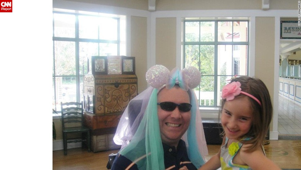 "Izzy and her dad  smile for the camera at Disney World. ""She bought those ears and while we were waiting for the bus at Disney, she put them on him and asked him to pose with her,"" Hayes said. ""She thinks it's hysterical to make him look silly so she does it at much as possible."""