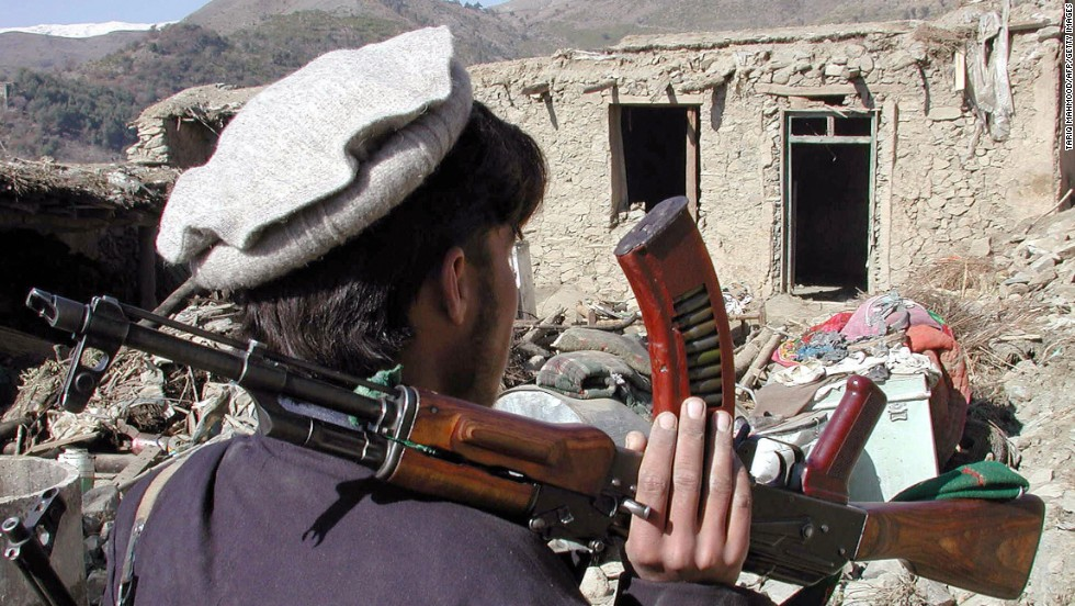 A Pakistani tribesman carries an AK-47 assault rifle after an air strike in Damadola, Pakistan, in 2006.