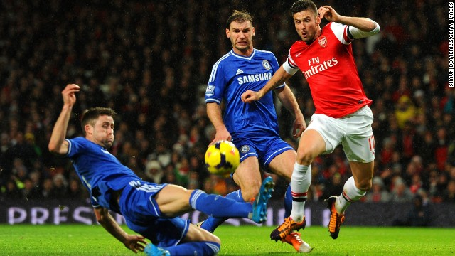 Gary Cahill of Chelsea tackles Olivier Giroud of Arsenal in a wet and windy match in north London