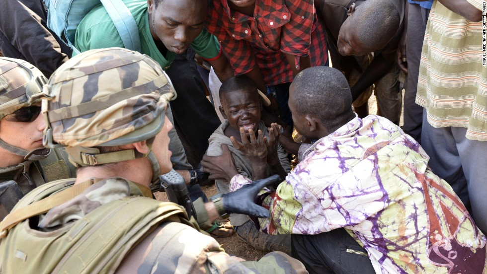 French troops and civilians try to comfort a crying boy near the airport in Bangui on December 23.