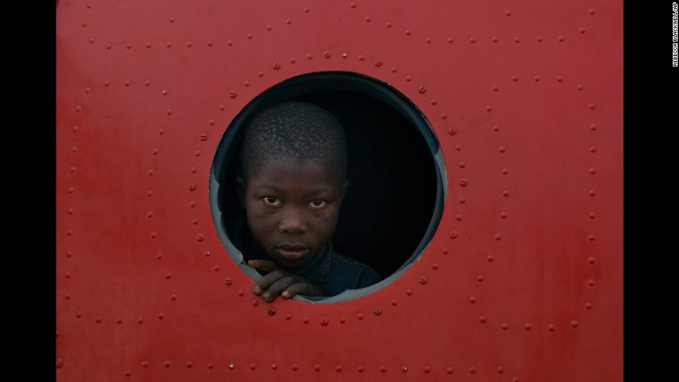 <strong>December 21: </strong>A boy looks out the broken window of a plane that serves as shelter in a makeshift camp housing more than 40,000 people at M'poko Airport in Bangui, Central African Republic. They've displaced by recent violence in the country.