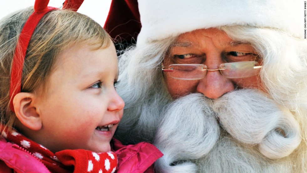 A man dressed as Santa Claus from Lapland, Finland, listens to a girl's Christmas wish on stage at a Christmas event organized by the Finnish Embassy in Seoul, South Korea, on Monday, December 23.