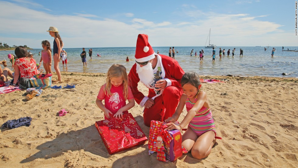 A man dressed as Santa Claus helps children open presents at Brighton Beach in Melbourne, Australia.