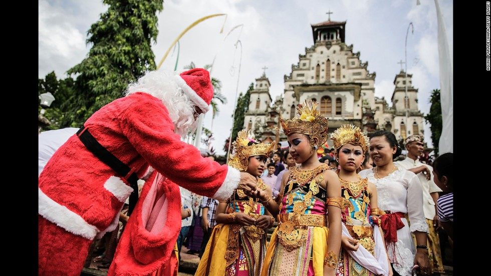 A man wearing a Santa Claus costume hands a gift to a dancer during Christmas celebrations at Hati Kudus Yesus Church in Palasari Village, Jembrana, Bali, Indonesia.