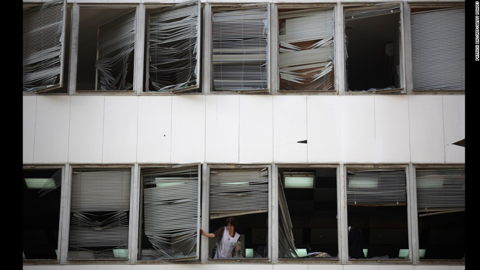 A woman removes shattered windows as she cleans an office near the site.