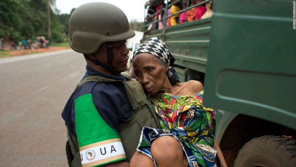 An African Union peacekeeper carries an elderly Cameroonian woman to a military vehicle in Bangui on December 27.