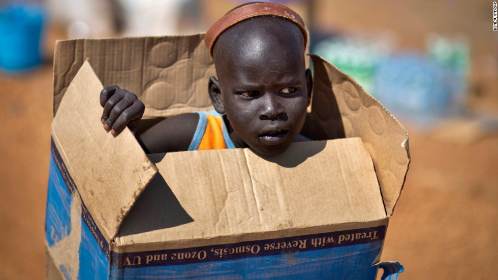 A displaced boy carries a cardboard box inside a U.N. compound in Juba on Friday, December 27.