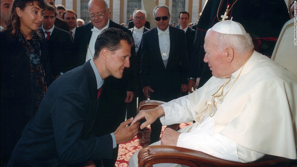 As a growing global celebrity, the German's fame took him away from the race track. Here he meets Pope John Paul II in 1999.