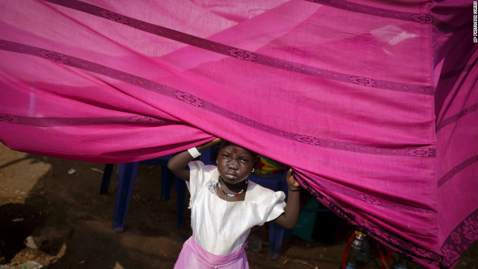 "DECEMBER 30 - JUBA, SOUTH SUDAN: A young girl peers from her makeshift tent at a United Nations compound which has become home to thousands of people displaced by the recent fighting. As the humanitarian crisis worsens, the U.N. said Friday the <a href=""cnn.com/2013/12/29/world/africa/south-sudan-conflict/index.html"">first of 5,500 additional peacekeepers had arrived in the country.</a>"