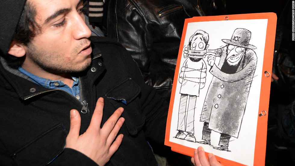 "Supporters of Dieudonne  argue that the issue of ""freedom of speech"" in France is at stake after Valls called for the comic's performances to be banned. Here a man poses with one of his drawings showing a Jewish character covering the mouth of another character with a gag reading ""freedom of speech."""