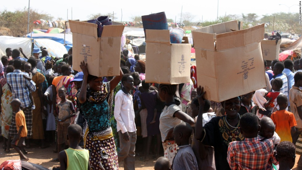 South Sudanese refugees carry relief supplies an a U.N. camp in Juba on Sunday, December 29.