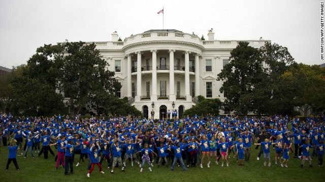 First Lady Michelle Obama is surrounded by school children doing jumping jacks during a 'Let's Move!' event, October 11, 2011.