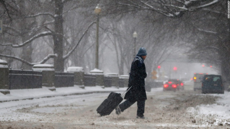 A man drags a suitcase on a snowy street in downtown Boston on January 2.