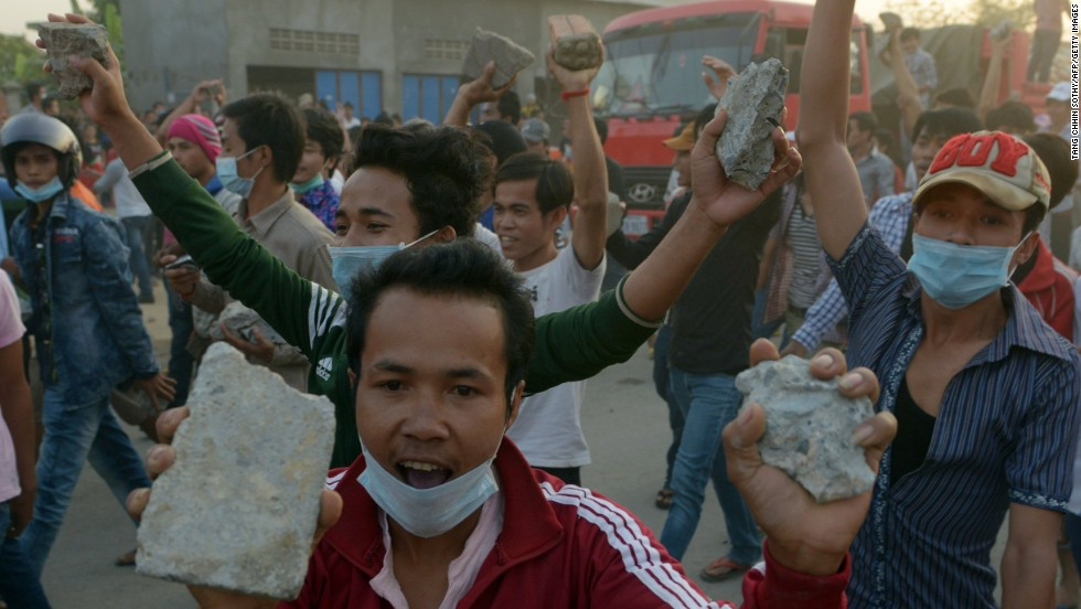 Cambodian garment workers carry rocks as they shout slogans after a brief clash with police during a protest to demand higher wages in front of a factory in Phnom Penh on January 2.