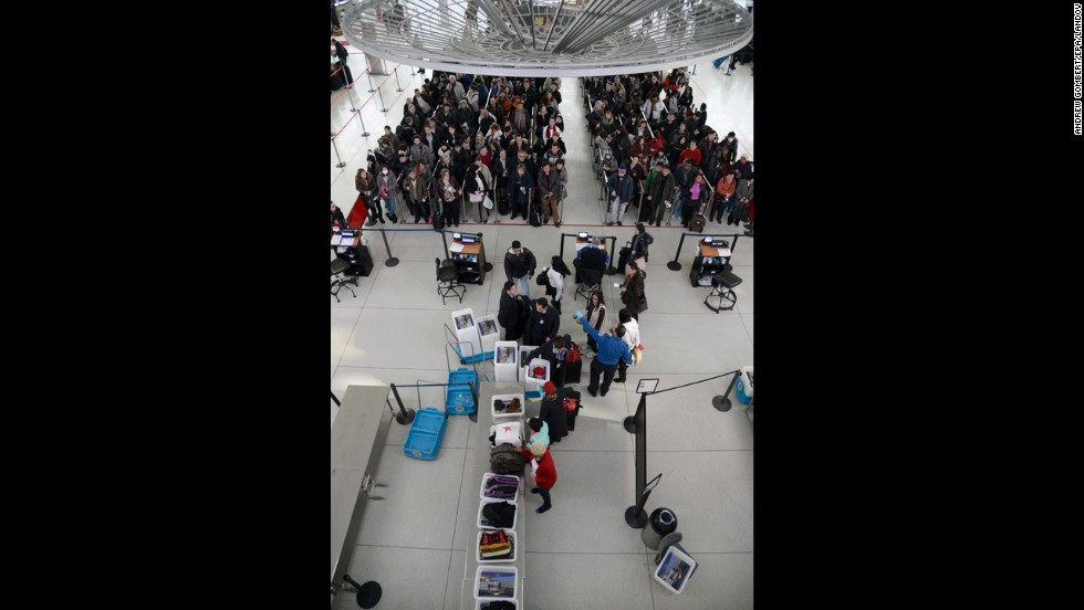 Passengers wait in line at a security checkpoint at JFK Airport on January 3.