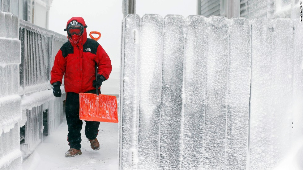 Michael Stanton walks between houses covered with ice in Scituate, Massachusetts, on January 3.