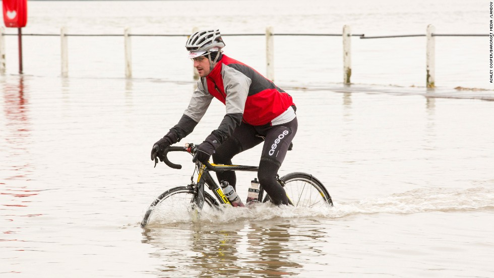A cyclist pedals through coastal floodwaters in Storth, England, on January 4.
