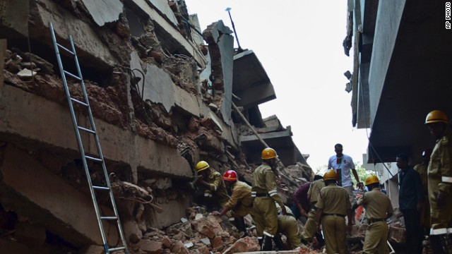 Rescue workers stand amid the debris of a building under construction that collapsed in Goa, India on 5 January.