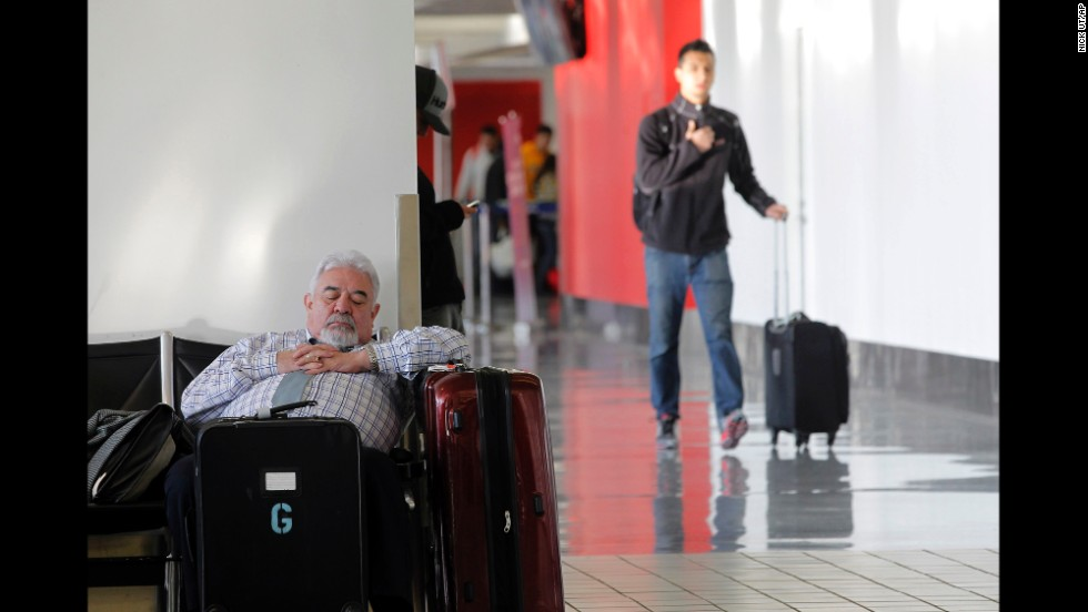 A passenger takes a nap inside Los Angeles International Airport on Friday, January 3, after his flight was canceled because of the weather on the East Coast.