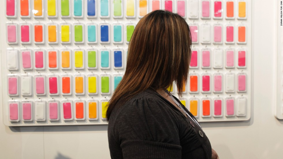 A woman looks at an array of cellphone cases made by Happy Plug.