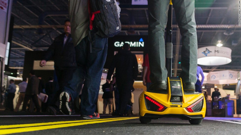 The Inmotion sensor-controlled vehicle, with passenger aboard, cruises the CES show floor.  The Segway-like device sells for $2,500.