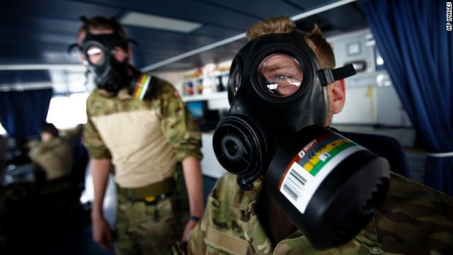 Member of Danish military personnel wearing a protective masks carry out emergency drills aboard the Danish frigate, on the sea between Cyprus and Syria, Friday, Jan. 3, 2014.
