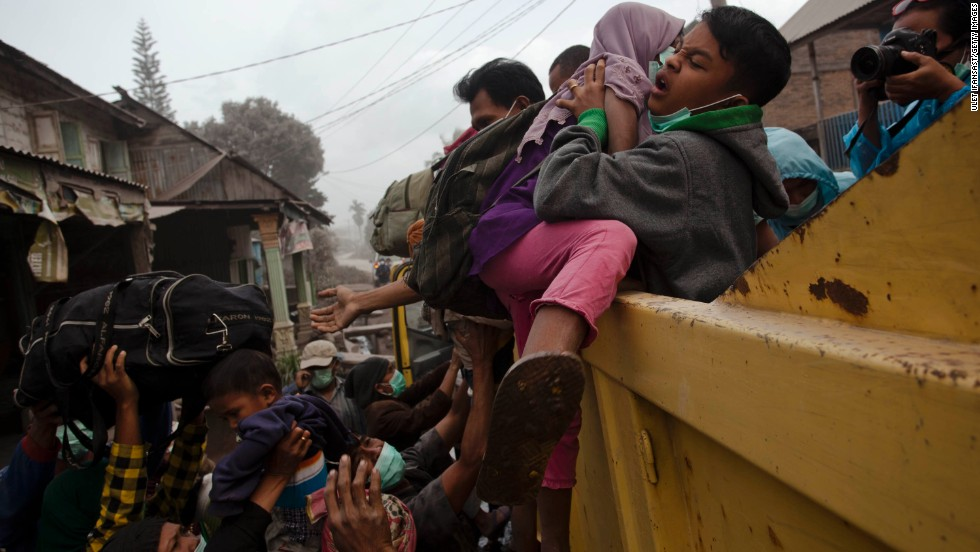 A man helps children onto a truck as residents are evacuated.