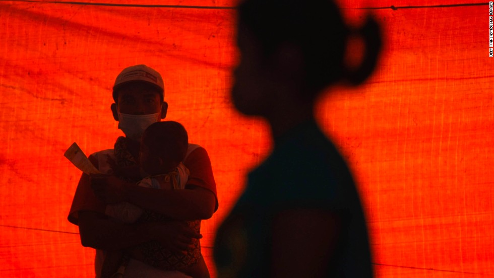A man holds his son at a temporary evacuation center.
