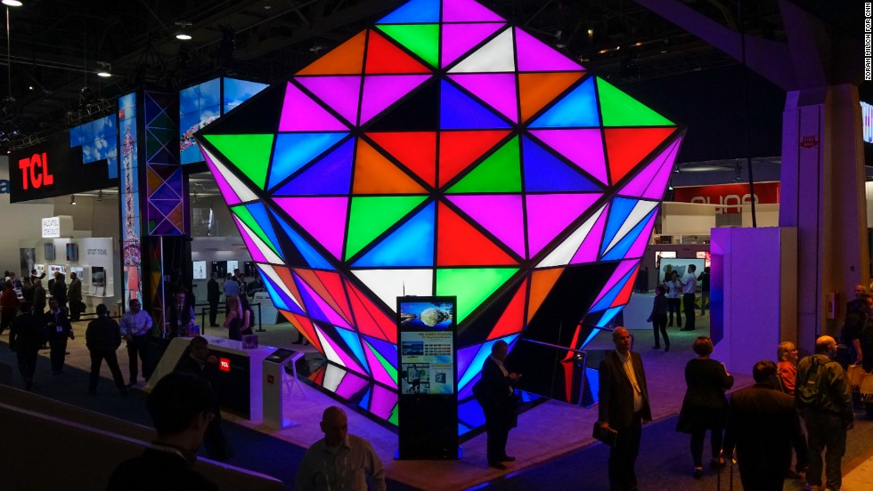 Attendees walk by the multicolored TCL television maker's booth.