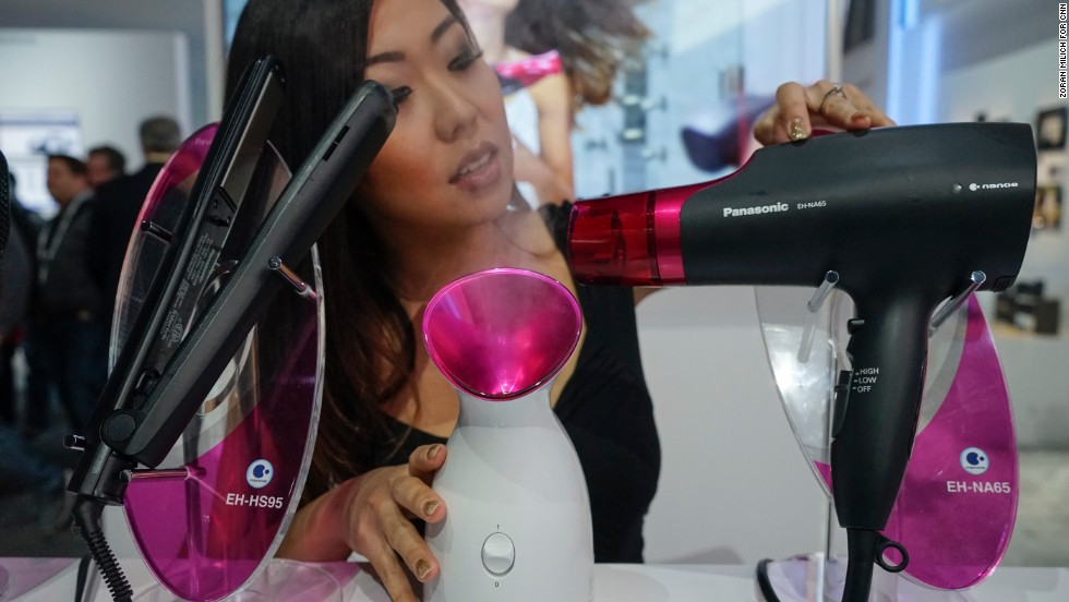 "A model demonstrates Panasonic's Nanoe  hair dryer, flat iron and facial steamers.  The devices use ""microscopic moisture particles"" and promise to keep hair and skin healthy. They are available at $179 each."