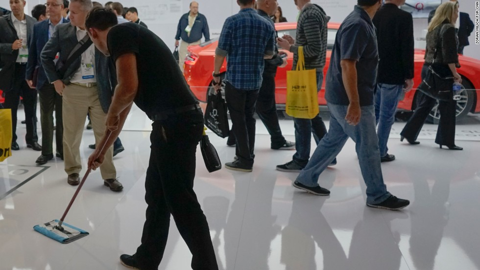 A worker polishes the floor of the Audi booth.