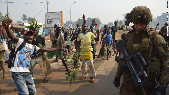 Anti Seleka demonstrators gesture on January 10, 2014 in Bangui as a French soldier part of the Sangaris operation holds position, a few hours before Central African Republic President Michel Djotodia stepped down under regional pressure