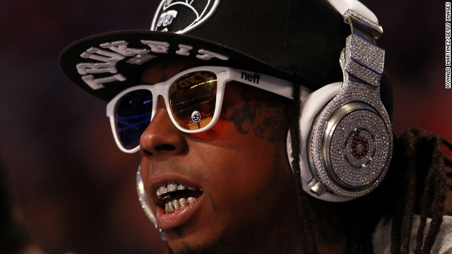 Hip-hop artist Lil' Wayne, wearing diamond-studded Beats headphones, sits courtside during the 2012 NBA All-Star Game.