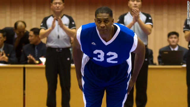 Former NBA star Charles D. Smith bows to North Korean leader Kim Jong Un, seated above in the stands, before an exhibition basketball game with U.S. and North Korean players at an indoor stadium in Pyongyang, North Korea on Wednesday, Jan. 8, 2014. (AP Photo/Kim Kwang Hyon)