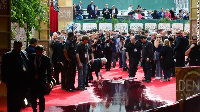 Staff clean up water on the red carpet after a pipe burst before the start of the event.