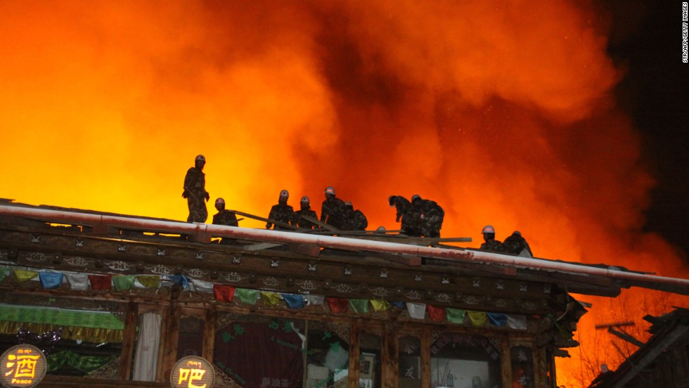 Firefighters work to put out a fire in Dukezong, Shangri-La county, Yunnan province in southwest China on Saturday.