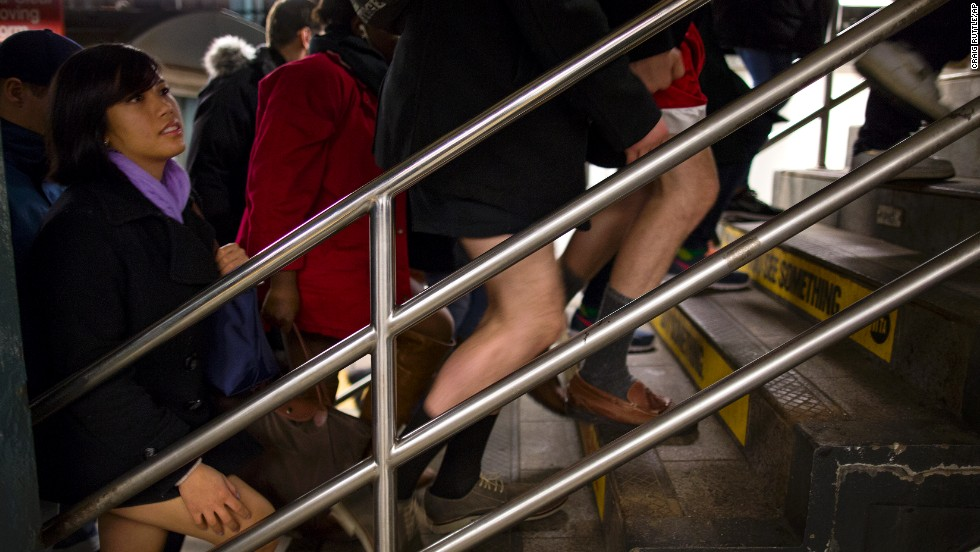 People with and without pants walk up a staircase at a subway station in New York.
