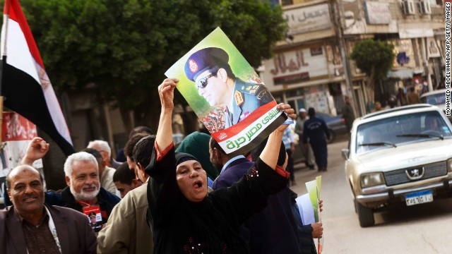 An Egyptian woman ululates as she holds a portrait of Egypt's Defence Minister General Abdel Fattah al-Sisi outside a polling station during the vote on a new constitution on January 14, 2014 in Kafr el-Sheikh.
