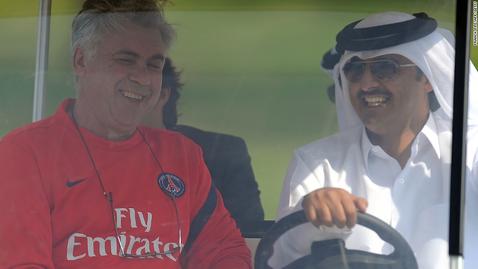 Paris Saint-Germain's coach Carlo Ancelotti rides in a golf buggy with Qatari Crown Prince Sheikh Tamim bin Hamad al-Thani, the French football club's owner.
