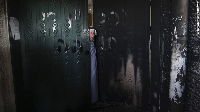 A Palestinian man stands on the doorway of a damaged mosque in the West Bank village of Deir Istiya on January 15, 2014.