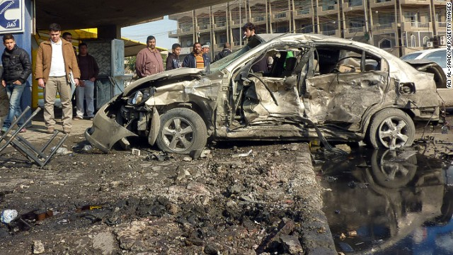 Iraqis gather at the site of a car bombing in central Baghdad on Wednesday.