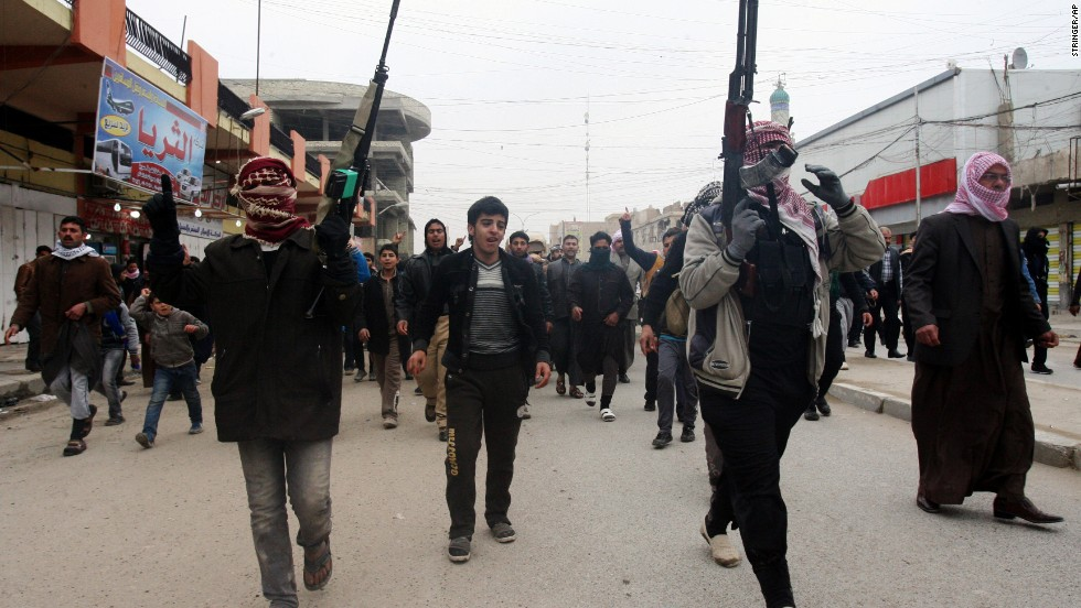 Mourners and Sunni gunmen chant slogans on Saturday, January 4, during the funeral of a man killed during clashes the day before.