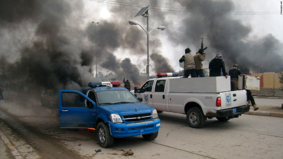 Al Qaeda fighters patrol a street in a commandeered police truck as another police vehicle burns in front of the main provincial government building in Falluja on Wednesday, January 1.