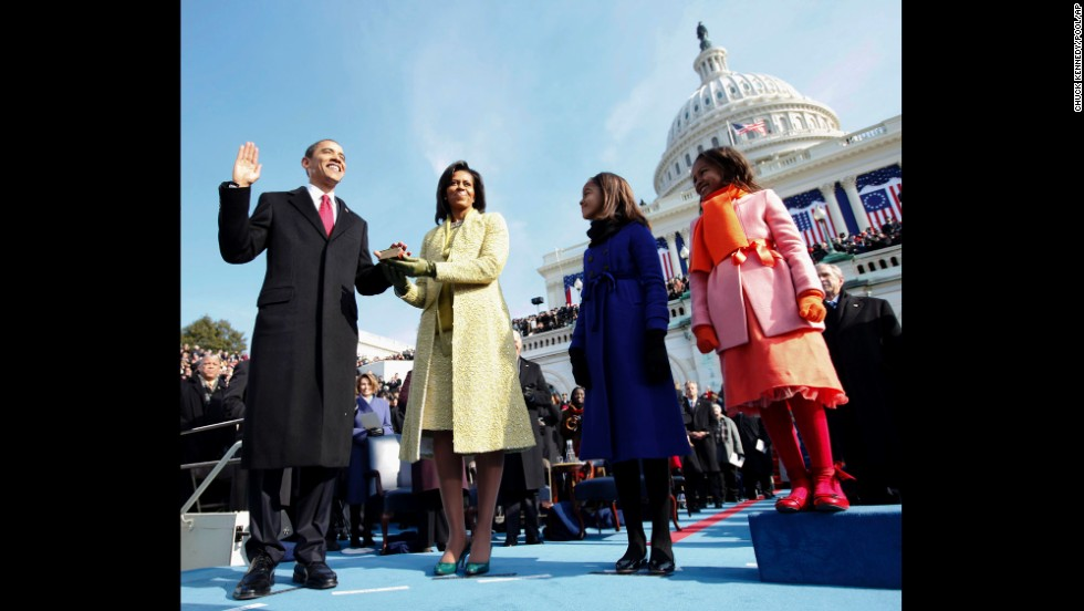 During his inauguration ceremony in Washington, Barack Obama takes the oath of office as his wife holds the Lincoln Bible.