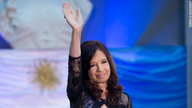 Argentina's President Cristina Fernandez waves in front of an Argentine flag during an event to celebrate the 30-year anniversary of the return of the democracy in Buenos Aires, Argentina, Tuesday, Dec. 10, 2013. (AP Photo/Victor R. Caivano)