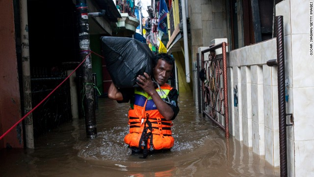 A man brings his belonging through the flooded area on January 13, 2014 in Jakarta, Indonesia.