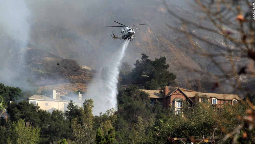 A helicopter drops water over homes in Glendora on January 16.