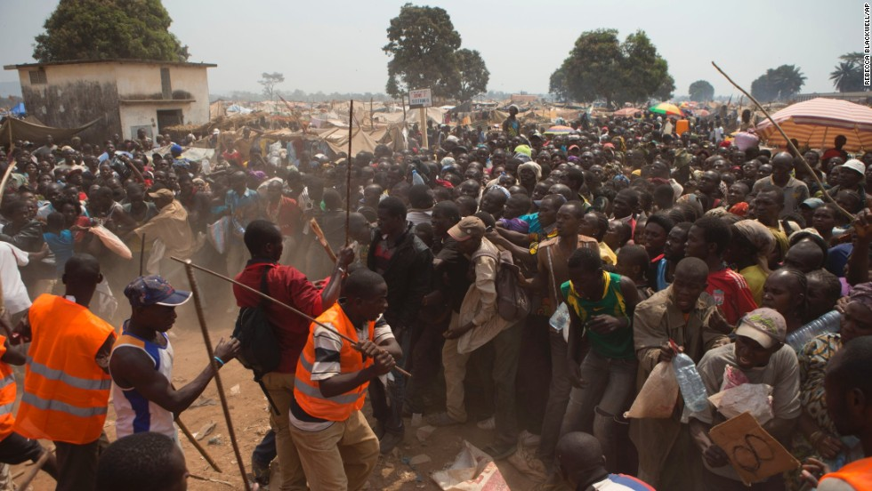 Security volunteers use sticks to fend off people trying to enter a food and supplies distribution point at a makeshift camp at Bangui M'Poko International Airport on Thursday, January 9.