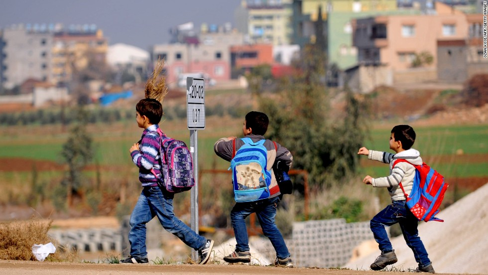 Syrian children walk on the street after attending school January 18 in Hatay.