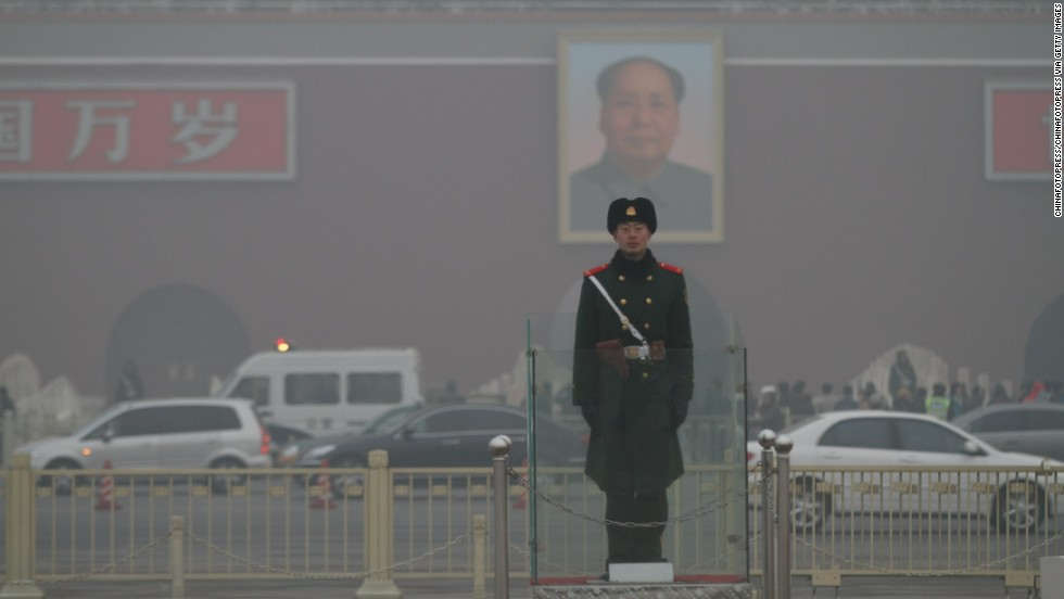A police officer stands guard in Beijing's Tiananmen Square on January 16. The co-author of a new study recommends increasing the efficiency of manufacturing processes and re-examining energy production to decrease pollution in China.